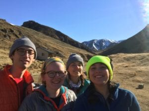A group of students pausing on a hike for a posed photo with mountains in the background.